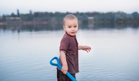The cheerful fair-haired kid is happy and smiles. A child and a lake stock image
