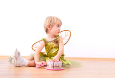 Cheerful fairy little girl cutting toy cake Royalty Free Stock Photography