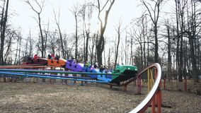 Cheerful families ride on the rainbow ride at the amusement park in the spring in Bobruisk, Belarus 03.09.19