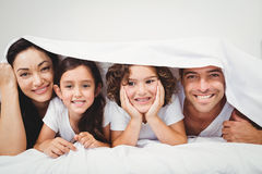 Cheerful family below blanket on bed Royalty Free Stock Image