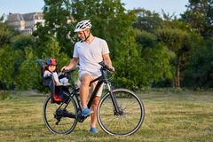 Cheerful family biking in park. Father and two girs ride in the city park. Weekend trip. Active life concept Royalty Free Stock Photography