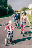 Cheerful family biking in park. At sunny autumn day Stock Photos