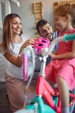 Cheerful family buying new bicycle and helmet for happy girl in bike shop. Cheerful family buying new bicycle and helmet for happy cute girl in bike shop royalty free stock photo