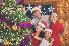 Cheerful family celebrating Christmas together. Cheerful family celebrating Christmas at home with a Christmas tree while wearing a Santa hat Royalty Free Stock Image