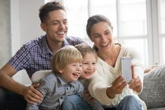 Cheerful family with children laughing taking selfie together on royalty free stock image