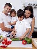 Cheerful family cooking vegetables together Stock Photos