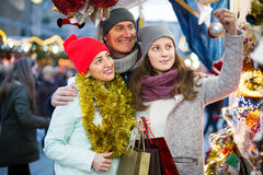 Cheerful family couple with teen daughter choosing Christmas dec Stock Photo