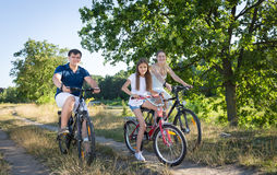 Cheerful family cycling in meadow at hot sunny day Stock Photography