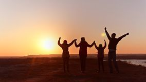 Cheerful family dances on shore of lake. Silhouettes sunset. stock video footage