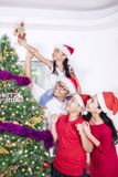Cheerful family decorating Christmas tree Stock Photography