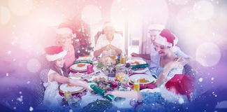 Composite image of cheerful family at dining table for christmas dinner. Cheerful family at dining table for christmas dinner against clouds covering snowcapped royalty free stock photo