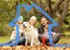 Cheerful family and dog overlaid with house shape in park. Digital composition of a cheerful family and dog overlaid with house shape in park Royalty Free Stock Photography