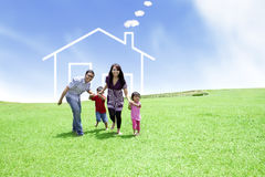 Cheerful family with a drawn house. Happy family running on field with a drawn house in background Stock Images