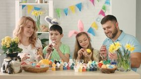 Cheerful family draws on Easter eggs together and mother takes selfie on the phone stock footage
