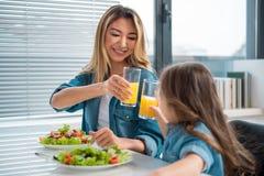 Cheerful family drinking orange juice in kitchen stock image