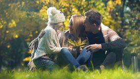 Cheerful family embracing school aged daughter in autumn park, perfect weekend. Stock photo royalty free stock photo
