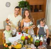 Cheerful family of four with bags of food Stock Photo