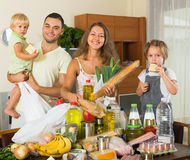 Cheerful family of four with bags of food. In house royalty free stock image