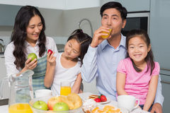 Cheerful family of four enjoying healthy breakfast in kitchen Stock Photography