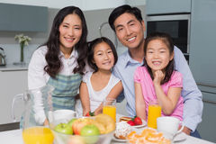 Cheerful family of four enjoying healthy breakfast in kitchen. Portrait of a cheerful family of four enjoying healthy breakfast in the kitchen at home royalty free stock photo
