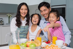 Cheerful family of four enjoying healthy breakfast in kitchen. Portrait of a cheerful family of four enjoying healthy breakfast in the kitchen at home royalty free stock images