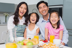 Cheerful family of four enjoying healthy breakfast in kitchen. Portrait of a cheerful family of four enjoying healthy breakfast in the kitchen at home stock photography