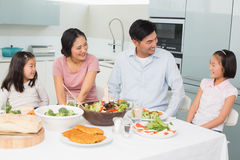 Cheerful family of four enjoying healthy meal in kitchen Stock Photo
