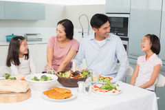 Cheerful family of four enjoying healthy meal in kitchen Royalty Free Stock Images