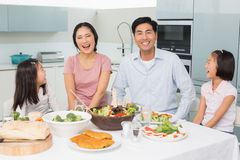Cheerful family of four enjoying healthy meal in kitchen. Portrait of a cheerful family of four enjoying healthy meal in the kitchen at home royalty free stock photos