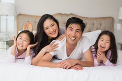 Cheerful family of four lying in bed. Portrait of a cheerful family of four lying in bed at home royalty free stock images