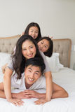 Cheerful family of four lying over each other in bed. Portrait of a cheerful family of four lying over each other in bed at home royalty free stock photo
