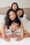 Cheerful family of four lying over each other in bed. Portrait of a cheerful family of four lying over each other in bed at home stock photos