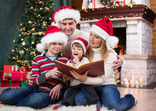 Cheerful family of four reading together on Royalty Free Stock Photo