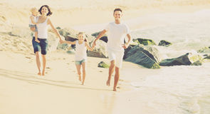 Cheerful family of four running on sandy beach Stock Images