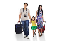 Cheerful family going to holiday. Portrait of asian family walking in studio while carrying luggage for holiday Royalty Free Stock Photos
