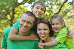 Cheerful family in green shirts Stock Images