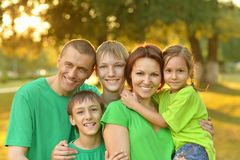 Cheerful family in green shirts. Walking in the summer park stock photography