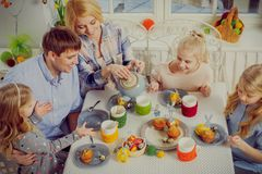 Cheerful family having fun and enjoying flavored tea and cupcakes. Stock Photo