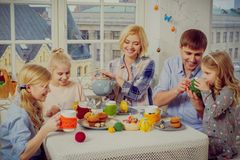 Cheerful family having fun and enjoying flavored tea and cupcakes. Royalty Free Stock Image