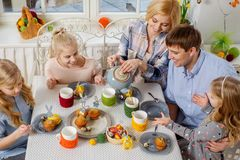 Cheerful family having fun and enjoying flavored tea and cupcakes. Royalty Free Stock Images