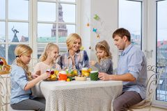 Cheerful family having fun and enjoying flavored tea and cupcakes. Royalty Free Stock Photography