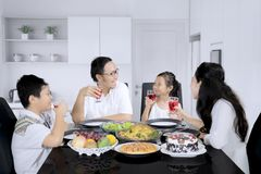 Cheerful family having lunch in the kitchen. Image of Cheerful family talking each other while having lunch in the kitchen royalty free stock photography