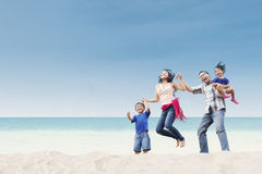 Cheerful family jumping at beach Royalty Free Stock Image