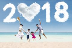 Cheerful family jumping under numbers 2018. Cheerful family jumping together under clouds shaped numbers 2018 and heart. Shot in the beach Royalty Free Stock Images