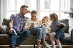 Cheerful family with kids laughing watching funny video on smart Stock Photography