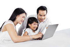 Cheerful family with laptop in studio Stock Photography