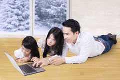 Cheerful family with laptop on wooden floor Royalty Free Stock Image