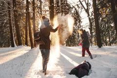 Cheerful family laughing in winter forest Stock Photos