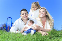 Cheerful family lay in grass of a playground Royalty Free Stock Photos