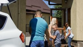 Cheerful family loading car with bags before vacation royalty free stock photos